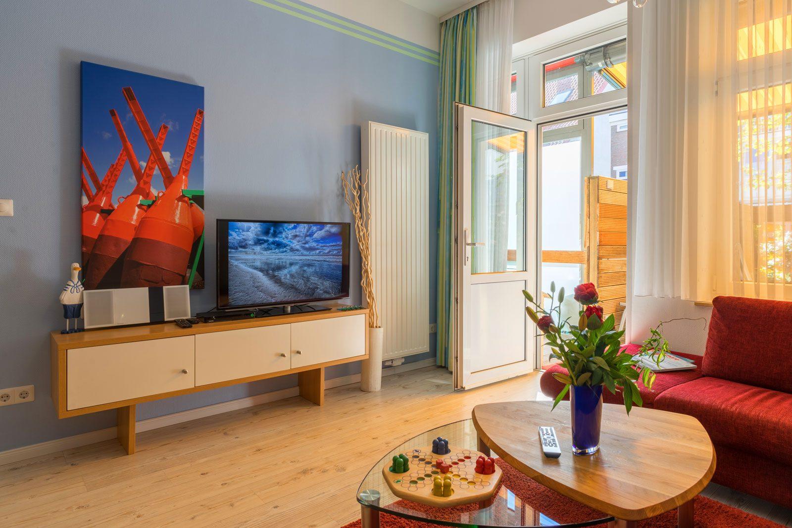 Wohnraum Apartment Sonnendeck mit Fernseher TV und grossem Bild mit roten Bojen