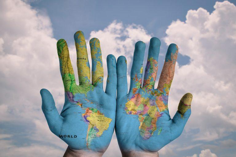 Haende mit aufgedruckter Weltkarte vor Wolkenhimmel