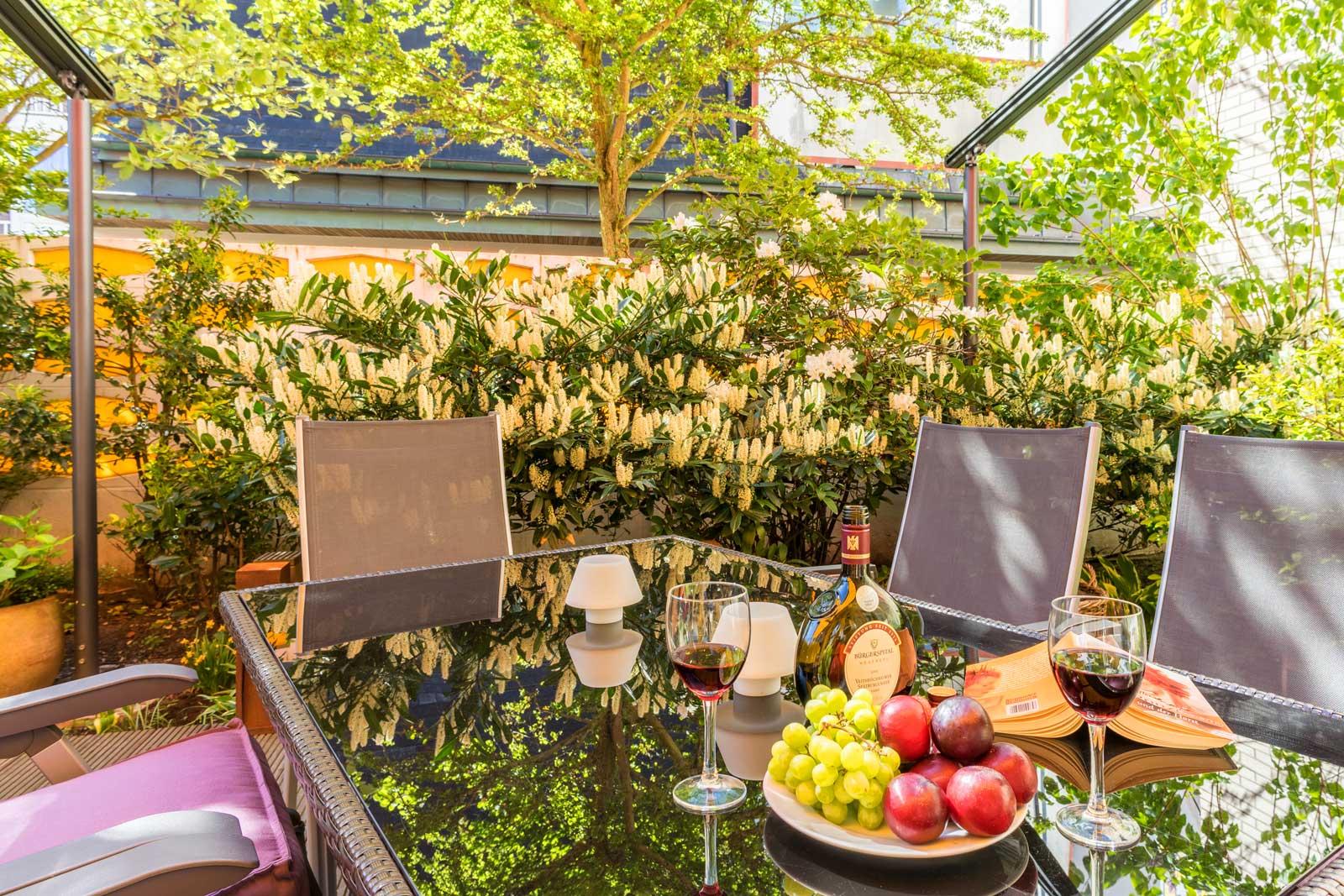 Terrasse mit gedecktem Tisch, Wein und Obst, Apartment Achterdeck