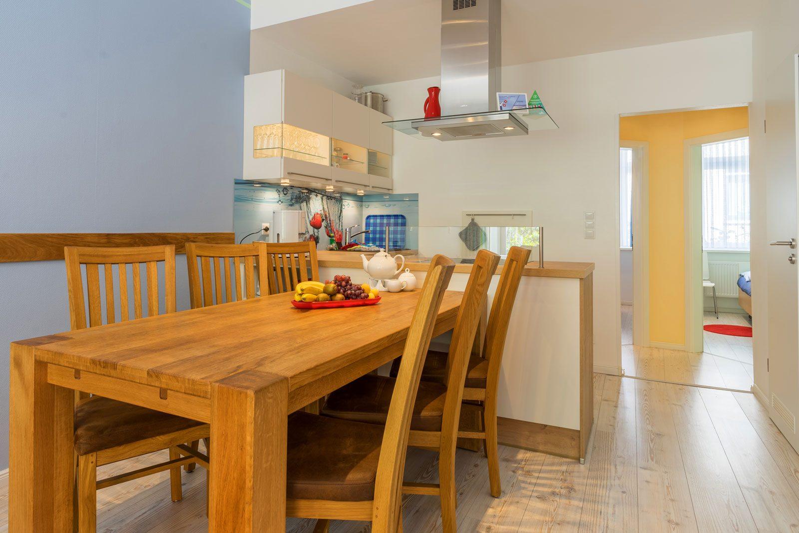 Holz-Esstisch mit sechs Stuehlen Apartment Achterdeck mit Blick auf Kueche