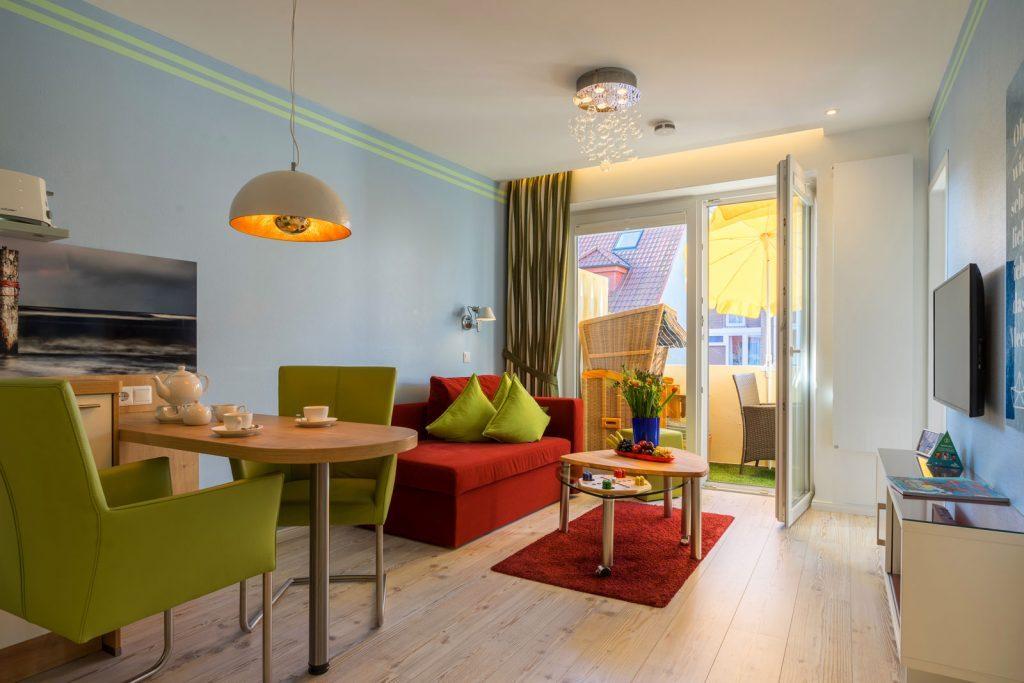 Esstisch und Wohnraum mit Blick auf Balkon und StrandkorbApartment Backbord