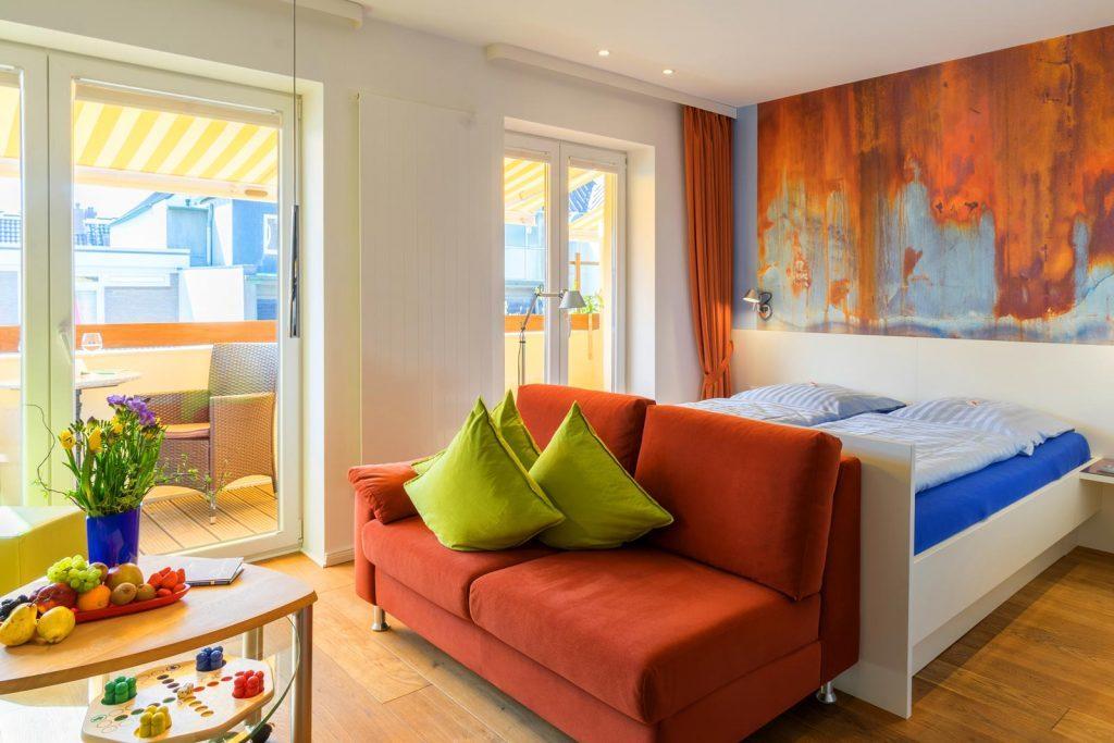 Couch und Bett mit Blick auf Balkon Apartment Kajuete ferienwohnungen
