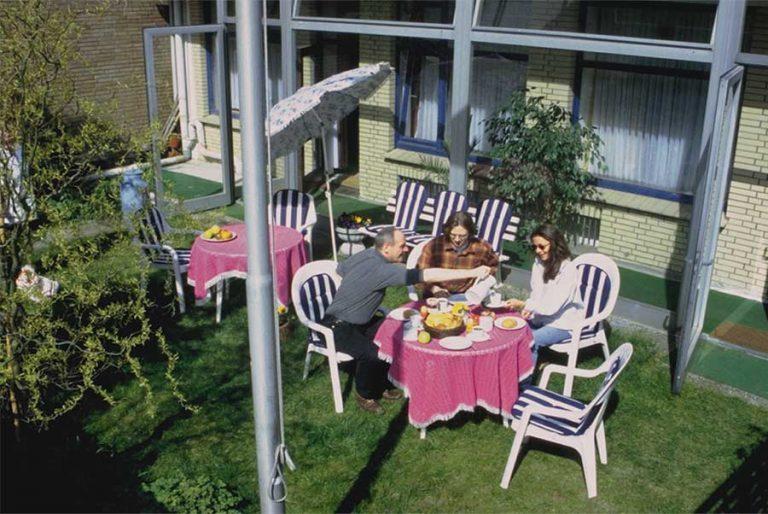 Garten mit drei Personen am gedeckten Tisch circa 2001